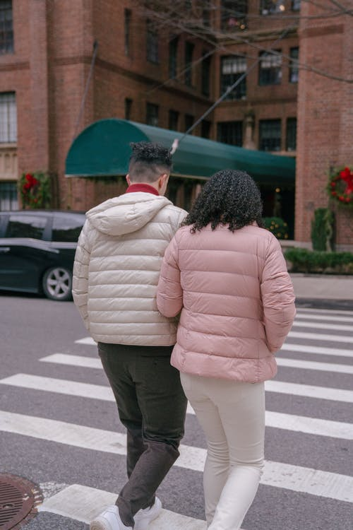 Couple crossing city street in daytime