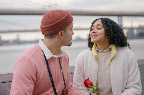 Romantic Hispanic couple with flower on seafront