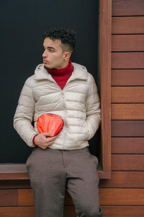 Serious Hispanic man with gift box