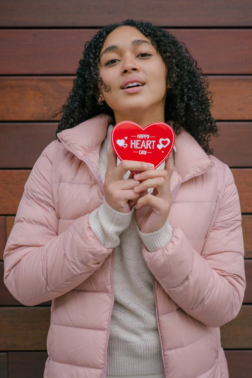 Hispanic female with curly hair looking at camera while standing near wooden building with heat shaped present during holiday celebration