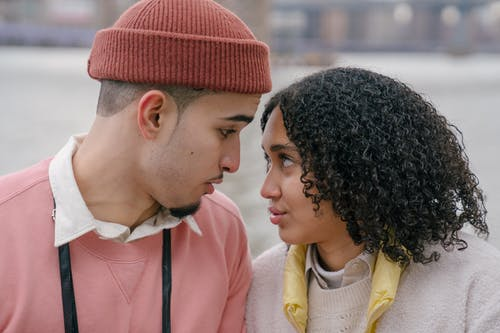 Side view of romantic Hispanic couple looking at each other while having date on waterfront near water on blurred background