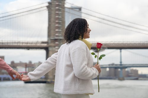 Cheerful Hispanic female with red flower holding hands with faceless boyfriend while strolling on embankment near sea against bridge during date