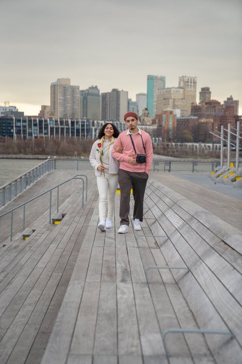 Full body of loving Hispanic couple strolling on wooden pathway and looking at camera while having date on waterfront in city