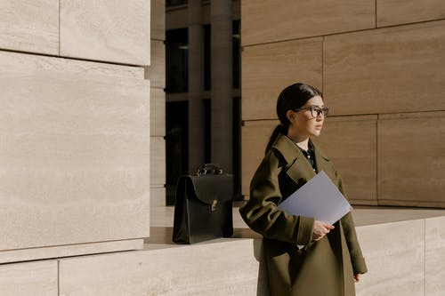 Woman Holding a Folder and Briefcase Near a Wall