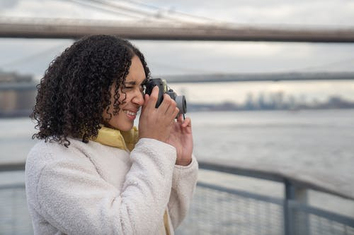 Side view of cheerful Hispanic female taking picture of sea while standing on waterfront near railing in city on blurred background