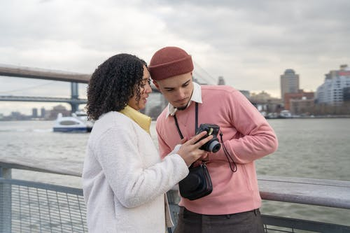 Latin American couple in warm clothes standing near fence and river under bridge near city with buildings and looking at photos on analog camera in daytime under cloudy gray sky