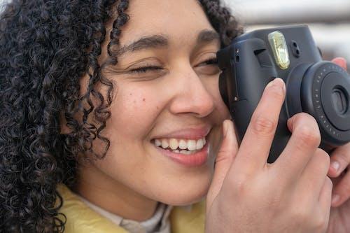Hispanic lady taking photo on photo camera in street