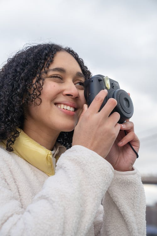 Smiling young Hispanic woman in outerwear standing in city street under cloudy gray sky while taking photo on analog photo camera in daytime