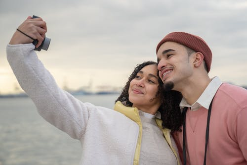 Smiling Latin American couple in warm clothes standing near river while taking self photo on analog camera in daylight under cloudy gray sky