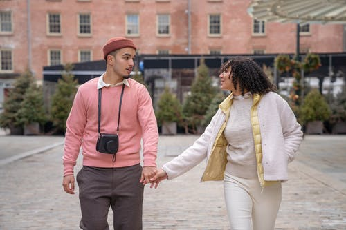 Positive young ethnic couple in stylish warm clothes holding hands while walking in aged district of city during vacation and looking at each other