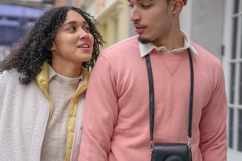 Happy young ethnic female with dark curly hair cuddling and talking to crop stylish boyfriend while walking together on city street