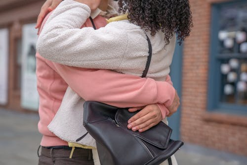 Crop faceless romantic couple embracing on street