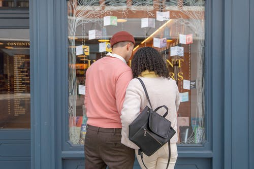 Back view of unrecognizable young couple in stylish outfits choosing books while standing on street near glass showcase of store during weekend