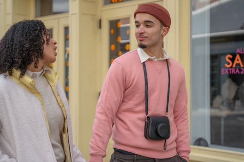 Happy young ethnic guy in stylish outfit with photo camera on neck holding hand and chatting with girlfriend during walk in city