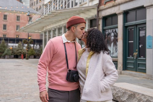 Romantic Hispanic couple in casual wear kissing while caressing on paved sidewalk on street near residential building during romantic date in city