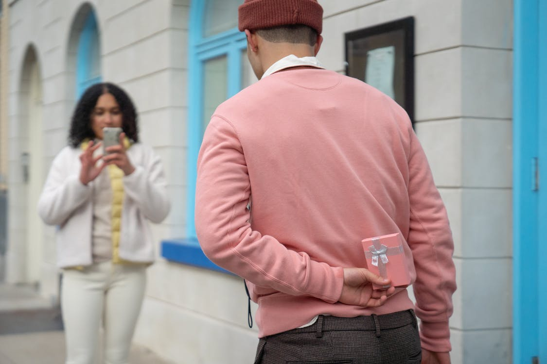 Blurred Hispanic woman taking photo of faceless boyfriend with pink gift box behind back during romantic date on street near building