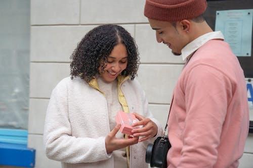Cheerful Hispanic woman receiving gift from boyfriend