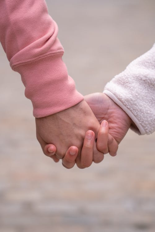 Person in Pink Long Sleeve Shirt Holding Babys Hand