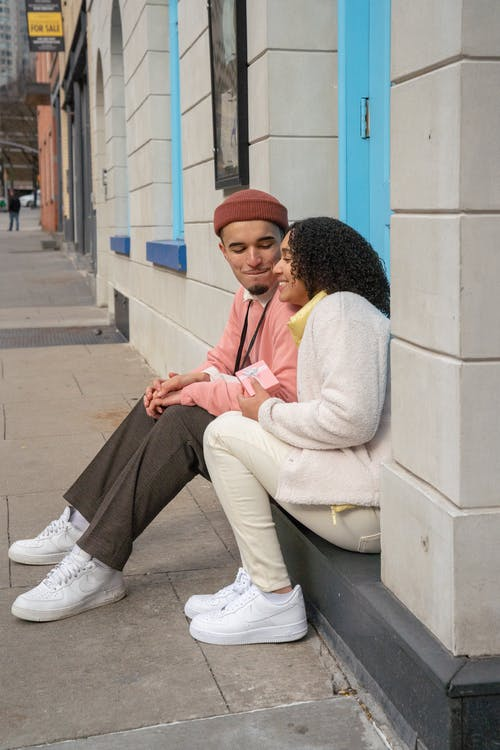 Young Hispanic positive couple smiling and resting on street