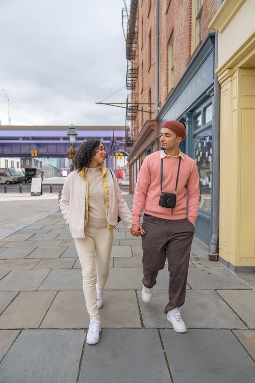 Trendy young ethnic couple holding hands while walking along street
