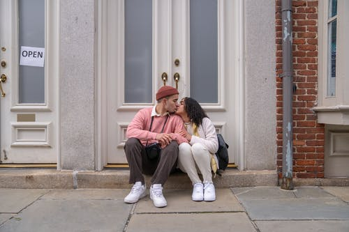 Enamored young ethnic couple kissing near doors of old building