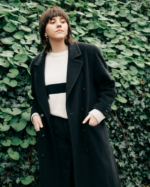 Confident woman in black coat standing near green bush and looking away