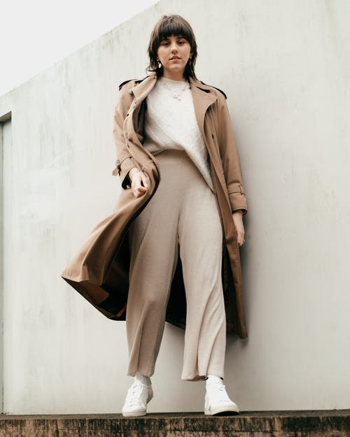 From below of full length of calm young female in trendy clothes and trench coat standing on light wall on street and looking at camera in daylight