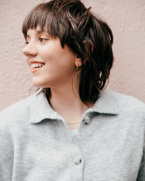 Positive young female with short brown hair in casual clothes smiling and looking away against light background in daylight