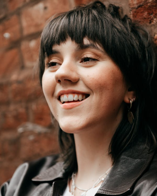 Smiling young female against brick wall