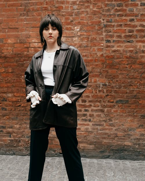 Confident young female in black leather jacket standing against brick wall
