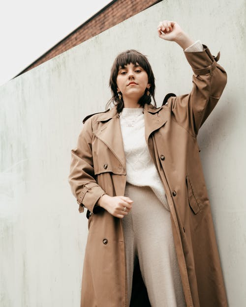From below of confident young woman with short dark hair in stylish trench coat standing with raised arm against concrete wall in daylight