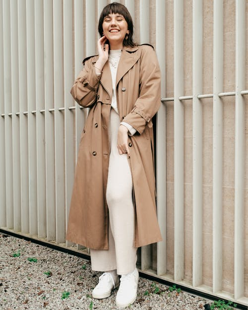 Full body of positive young female with short brown hair in trench coat and stylish clothes standing near high metal fence in daytime
