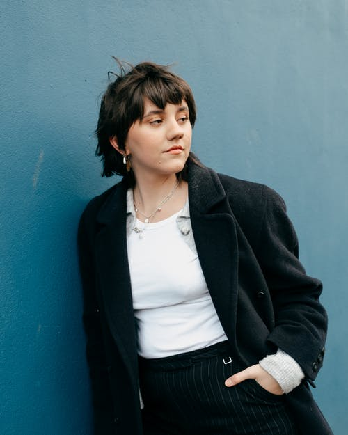 Confident young female with short brown hair in black jacket and stylish clothes standing with hand in pocket near blue wall and looking away in daylight