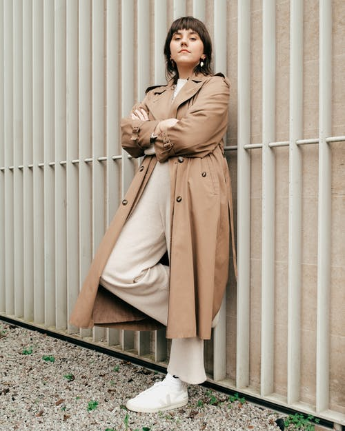 Full body of serious female with dark hair in stylish trench coat standing with crossed hands and leaning on high metal fence in daylight