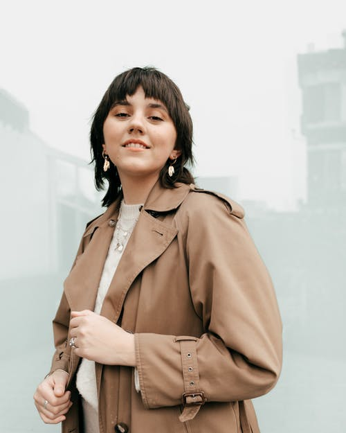 Self assured young female millennial with dark hair in trendy trench coat smiling and looking at camera while standing on street near building with glass walls
