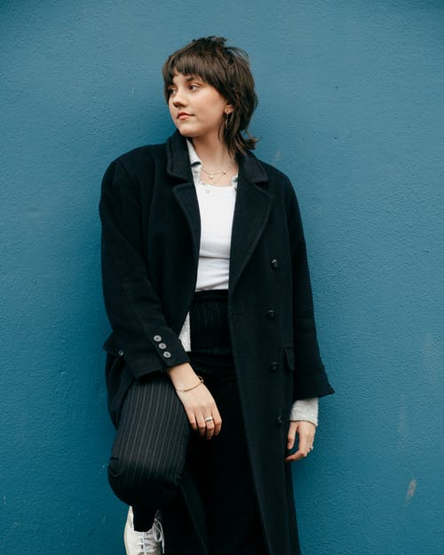 Stylish young female in trendy clothes and coat looking away while standing near stone blue wall in street in daylight