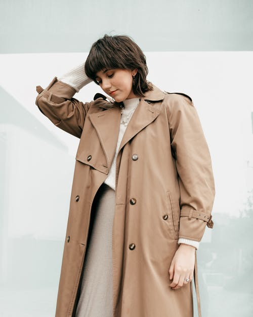 Calm young lady in trendy beige trench coat touching dark hair and looking down while standing on street