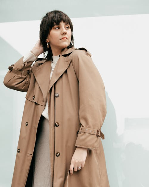 Stylish woman in coat looking away on street