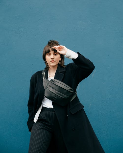 Serious female with bag near blue wall with raised arm