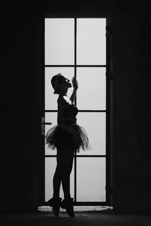Graceful ballerina in tutu standing against door