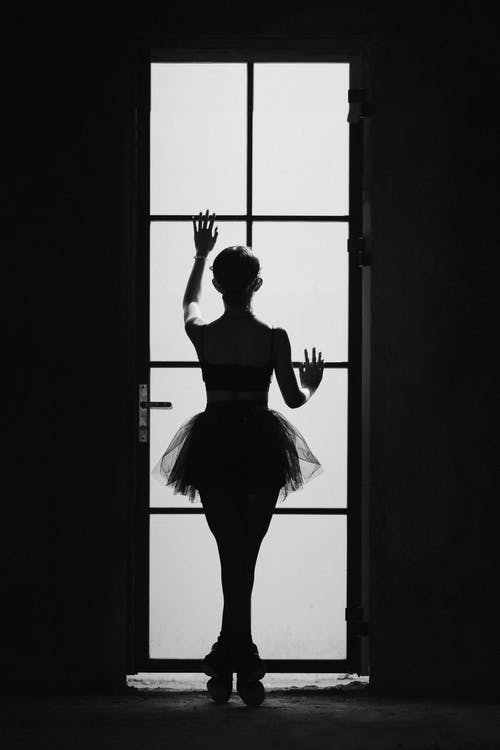 Black and white back view of anonymous female ballet artist silhouette standing on tiptoes against door