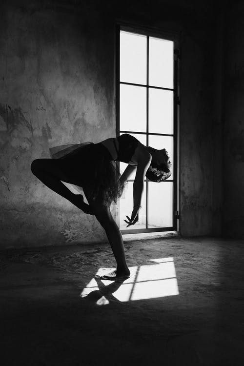 Woman Bending Her Body in Grayscale Photography