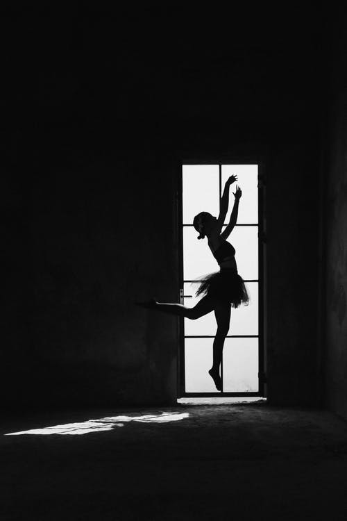Black and white side view of anonymous female ballet dancer showing choreographic movement with raised leg against door
