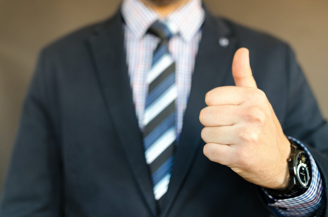 Visual of a Man In Black Formal Suit Jacket with his thumb up