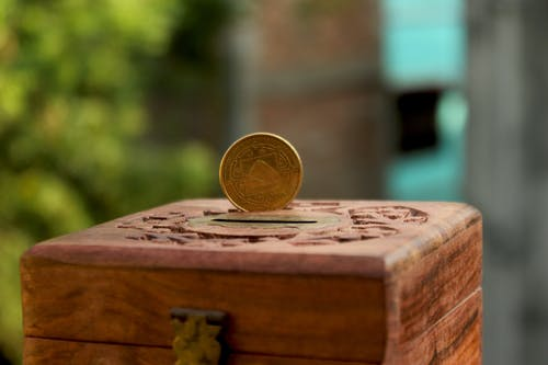 Gold Round Coin on Brown Wooden Table