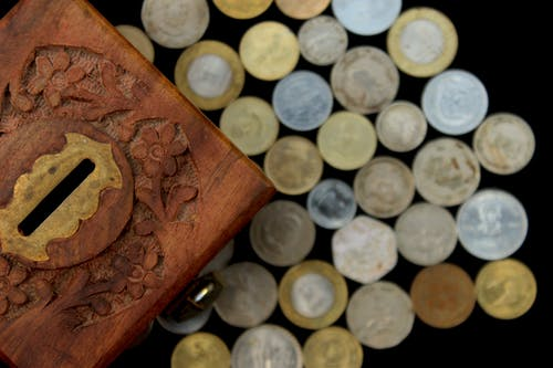 Silver Round Coins on Brown Wooden Box