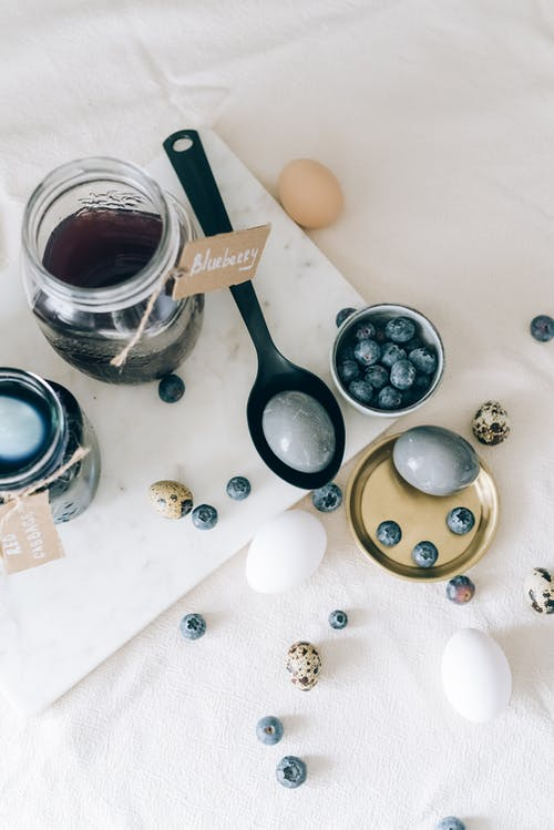 Blue Colored Eggs Beside A Bowl Of Blueberries