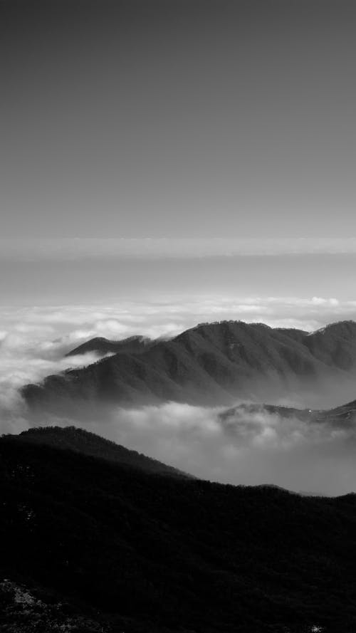 Black and white breathtaking view of rough rocky mountains peaks surrounded with thick clouds