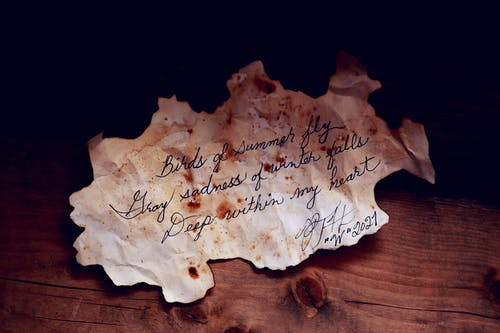 White Burnt Paper With Text On Brown Wooden Table