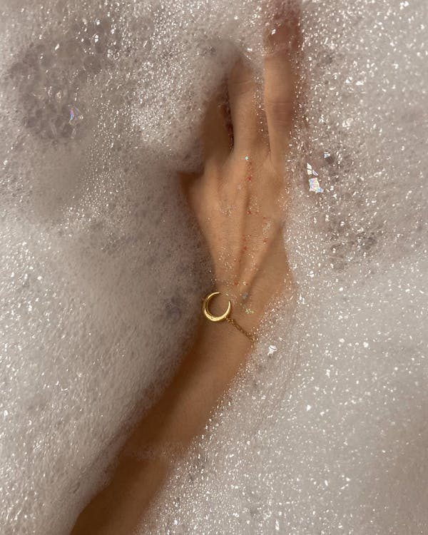 Woman with bracelet taking bath with foam